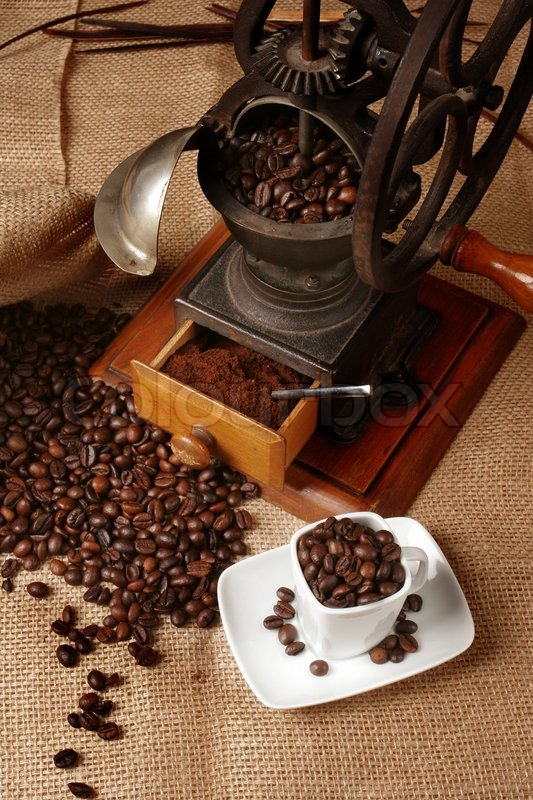 Grinder with coffee beans and a cup of espresso, stock photo