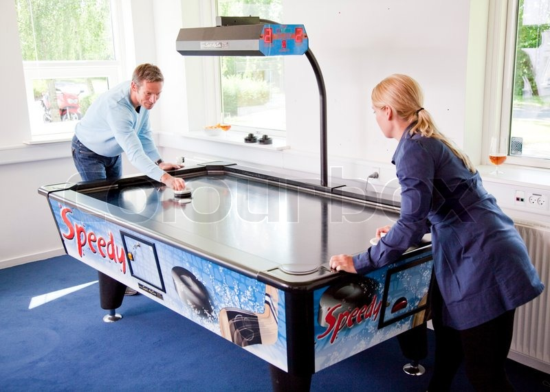 Business people having fun i the break/ recreation room. Colleagues playing air hockey in their recreation room/ break room, stock photo