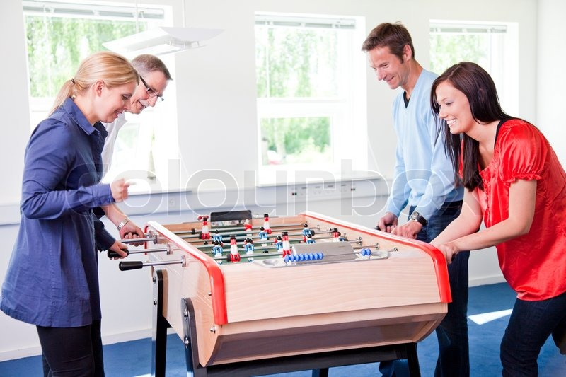 fun in the office. 4 colleagues playing tabletop football in the break room of their office business people having fun