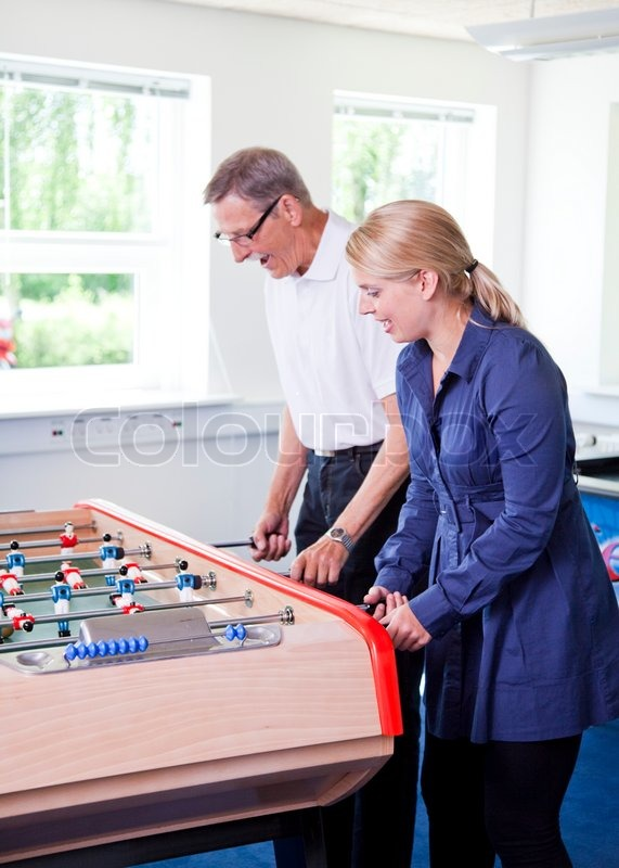 Business people having fun i the break/ recreation room. Colleagues playing tabletop football in the break room of their office. Business people havi, stock photo