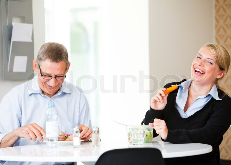 Stock image of 'Two colleagues sitting in the break room, having lunch and laughing. Business people having lunch/ lunch break.'