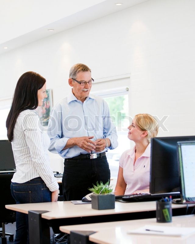 Stock image of 'Colleagues discussing a problem and helping each other.'