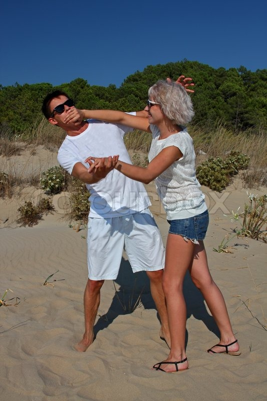 a couple of young people fighting for fun at a beach