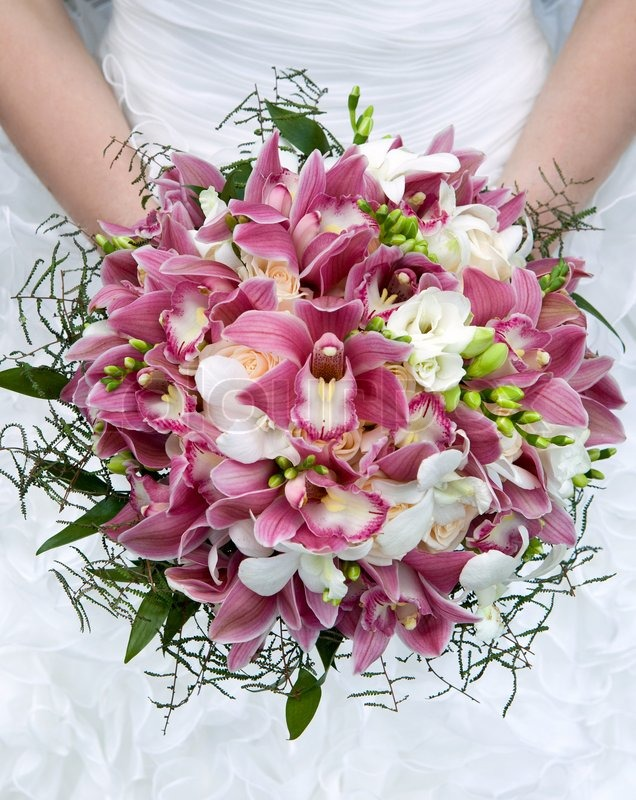Wedding bouquet. Bouquet of fresh flowers for the wedding ceremony. Bouquet of orchids, roses and other flowers in the bride's hands closeup. Bridal bouquet, stock photo