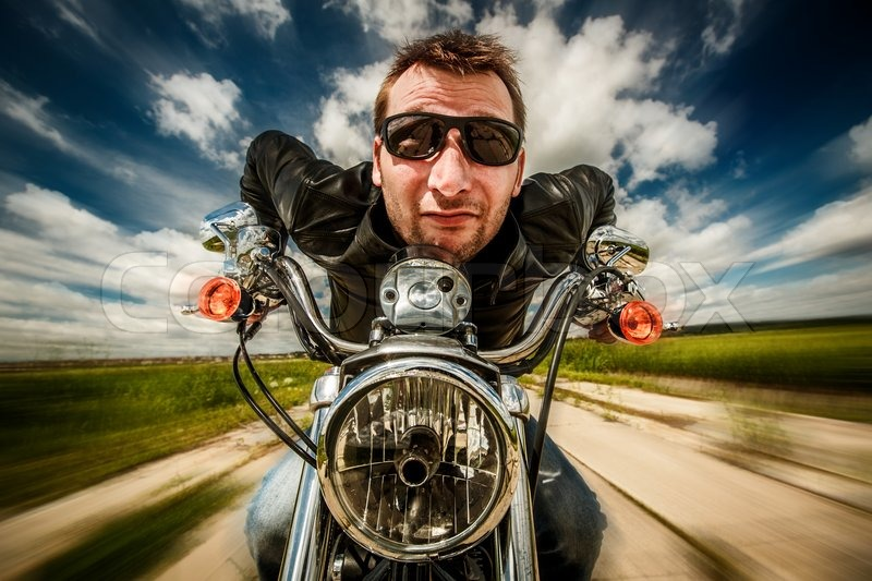 Funny Biker in sunglasses and leather jacket racing on the road (fisheye lens), stock photo