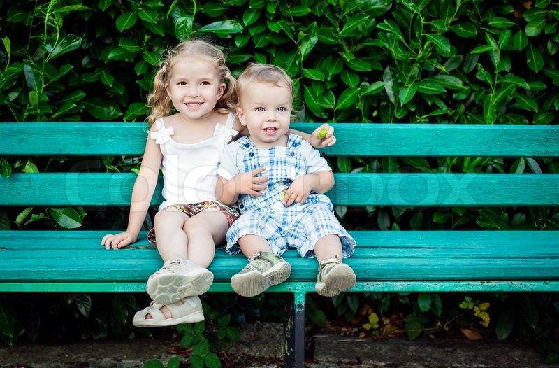 Funny little children brother and sister sitting on bench, stock photo