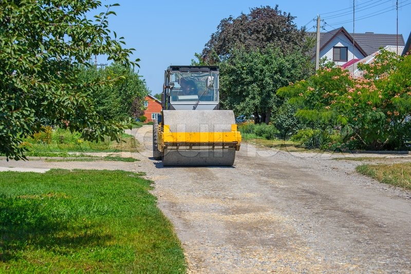 Road roller compacts the gravel on dirt road, stock photo