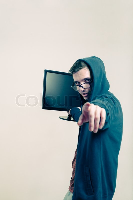 Man in hoodie holding monitor and pointing at you, stock photo