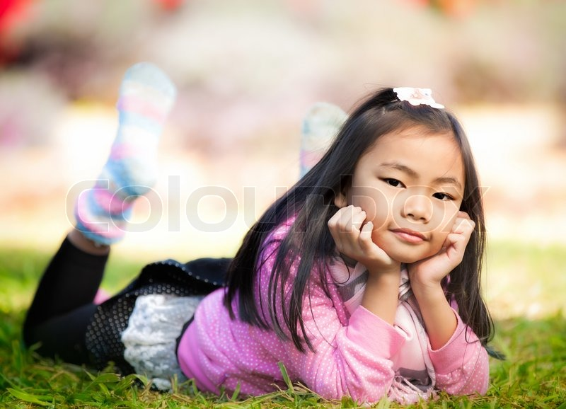 Little Asian Girl Smile And Resting On Green Grass In Cool And Stock Photo Colourbox