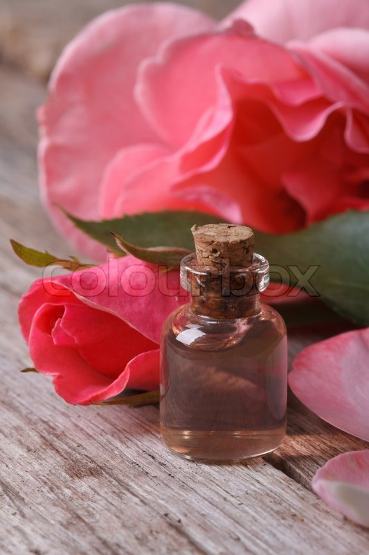 Rose water in a glass bottle on a background of pink roses close up vertical , stock photo