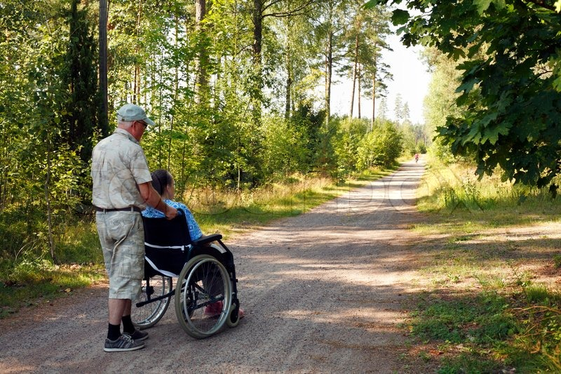 male assistant walking old woman in wheelchair on small