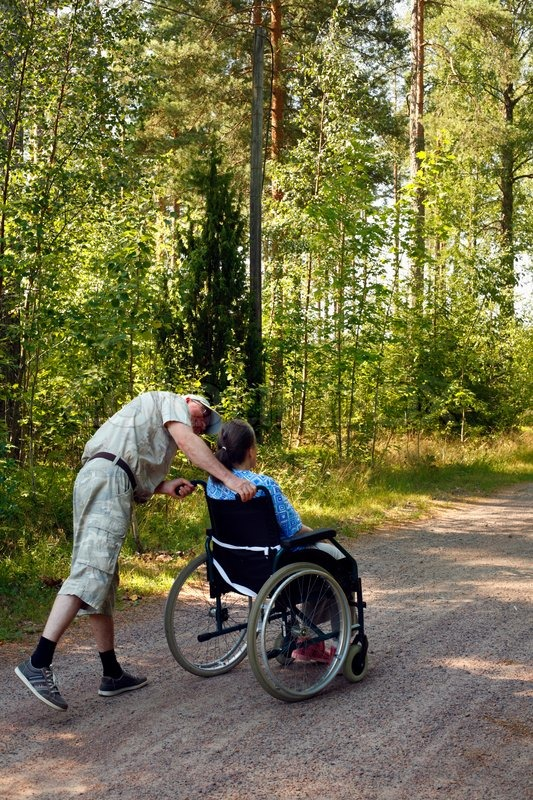 Mature Male Assistant Entertaining Old Woman In Wheelchair
