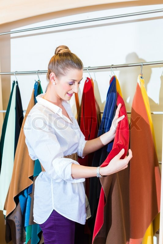 Young woman selecting seat cover for sofa in furniture store, stock photo