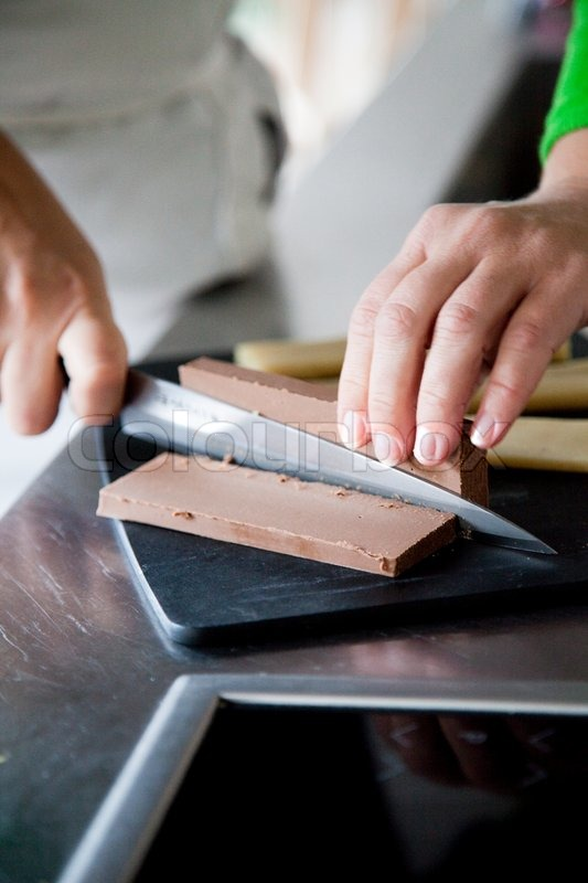 Stock image of 'A woman slicing nougat'
