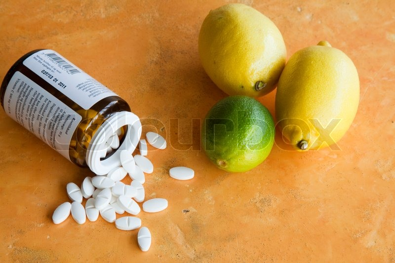 Stock image of 'Vitamin supplements and citrus fruits'