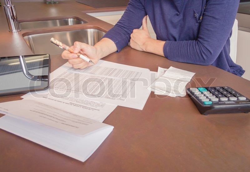 Unemployed and divorced woman with many debts reviewing her monthly bills, stock photo