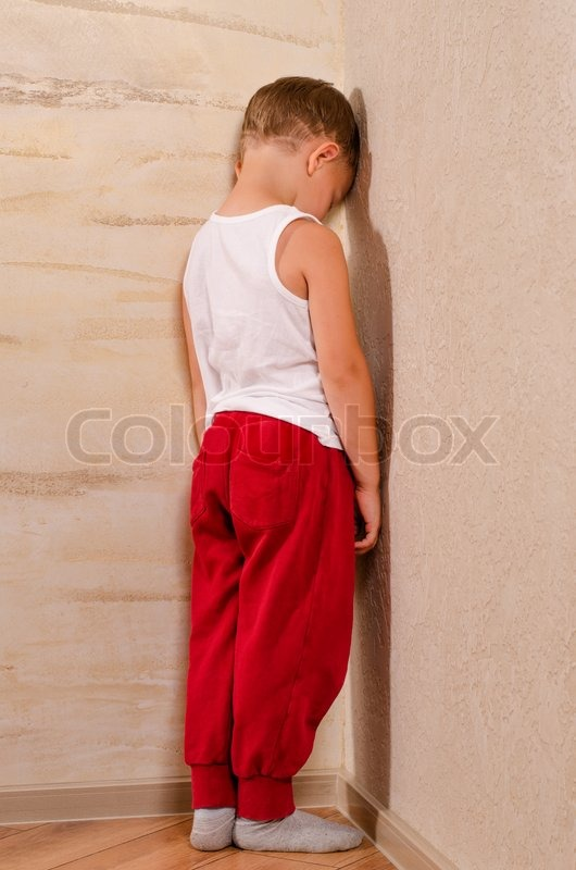 Standing In The Corner : Little boy standing in a corner sulking turning to watch