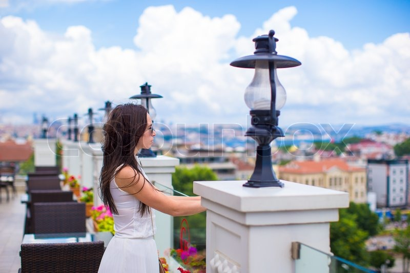 Young beautiful woman on the restaurant terrace with a stunning view of the city, stock photo