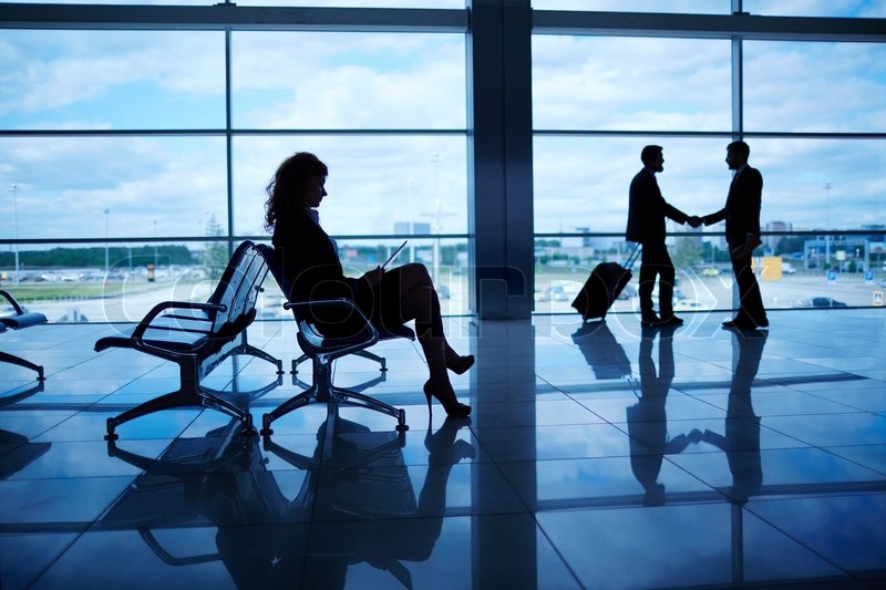 Outline of businesswoman sitting in airport on background of her colleagues handshaking by the window, stock photo