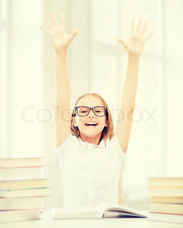Education and school concept - little student girl with books and hands up at school, stock photo