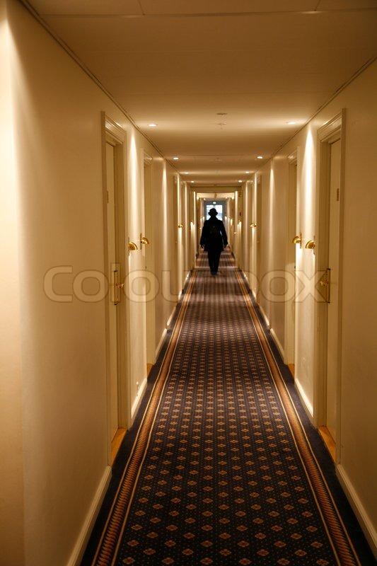 Long Foyer Jobs : Black dressed person walking down a long hotel corridor