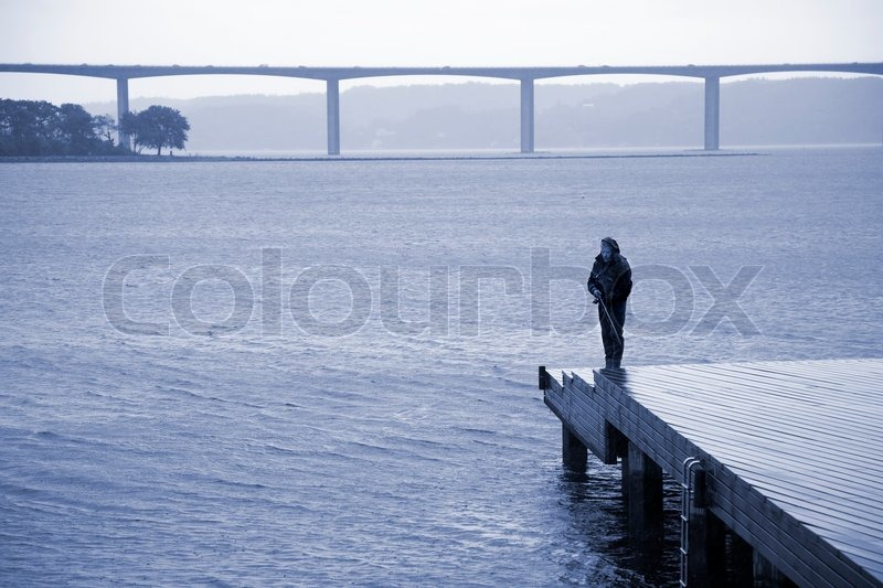 Angler in bad weather - Vejle Fjord bridge in the background - Denmark. Editorial, stock photo