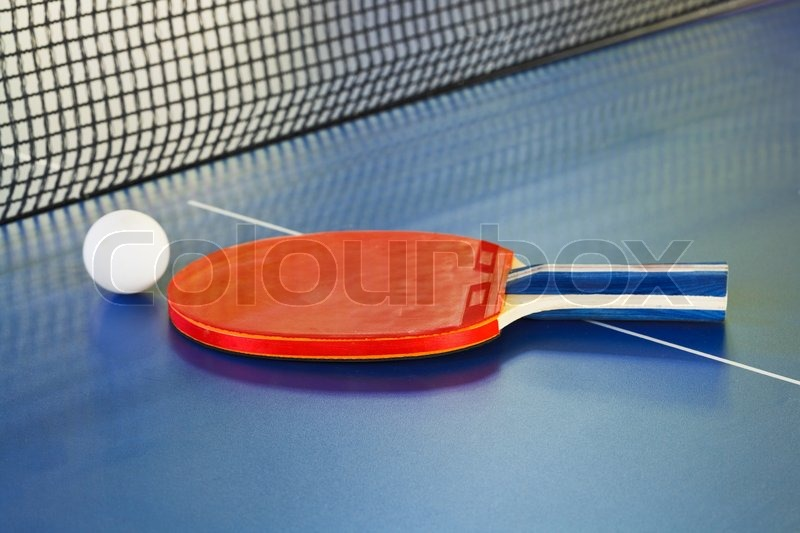 Red paddle, tennis ball on ping pong sport table close up, stock photo