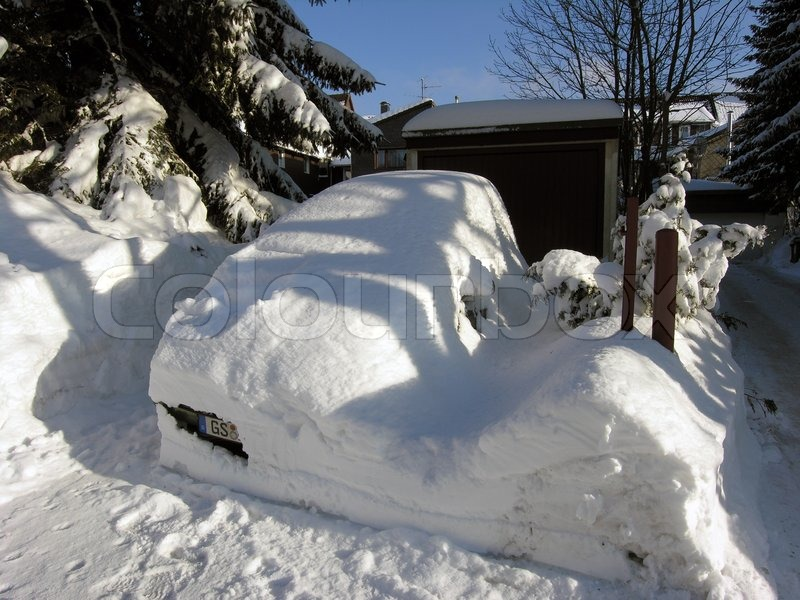 My white car. Car covered with snow in the winter blizzard, stock photo