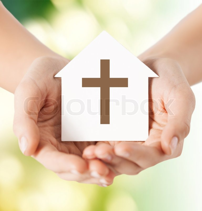 Religion, christianity and charity concept - close up of woman hands holding paper house with christian cross symbol over green background, stock photo