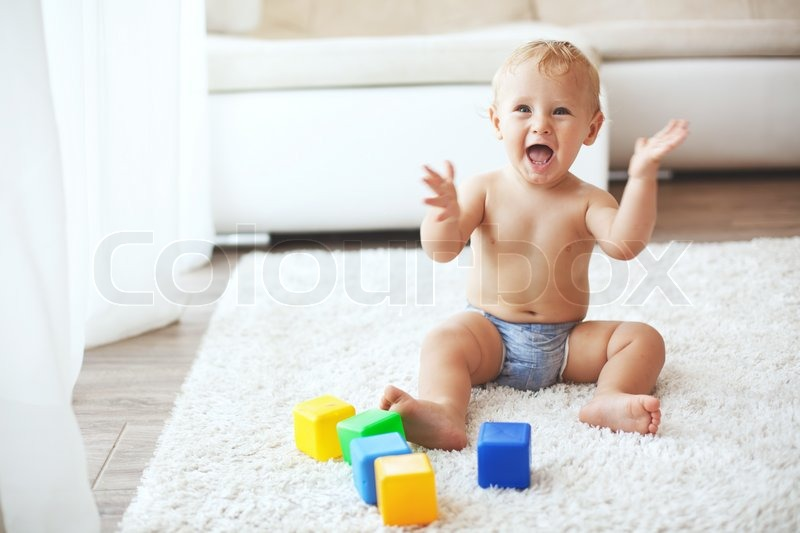 Toddler playing with toys on a white carpet at home, stock photo