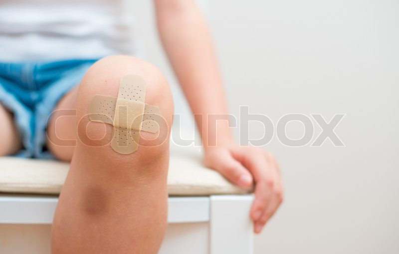 Child knee with an adhesive bandage and bruise, stock photo