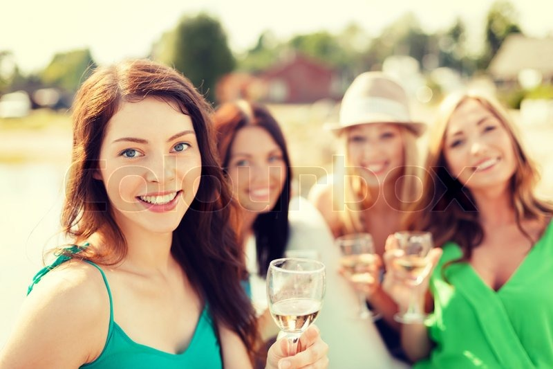 Summer holidays, vacation and celebration concept - smiling girls with champagne glasses, stock photo