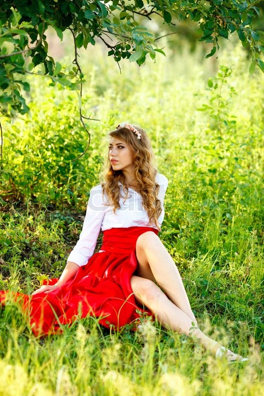 Portrait Of The Woman In Red Skirt Sitting Under The Tree