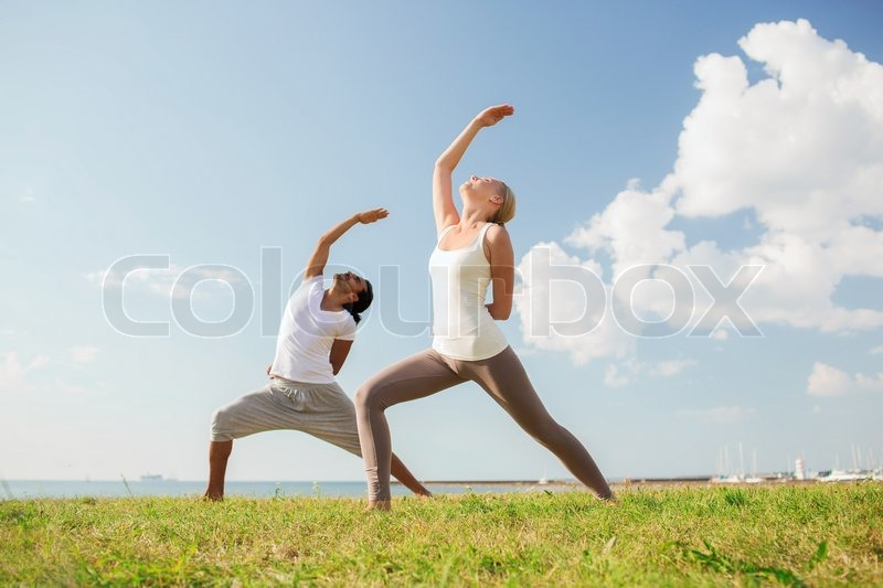 Fitness, sport, friendship and lifestyle concept - smiling couple making yoga exercises outdoors, stock photo
