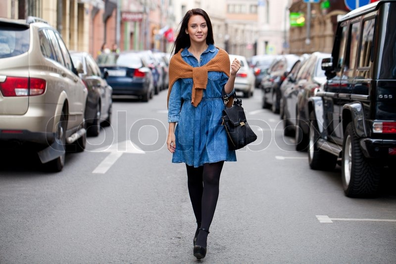 Beautiful young woman walking on the street , stock photo