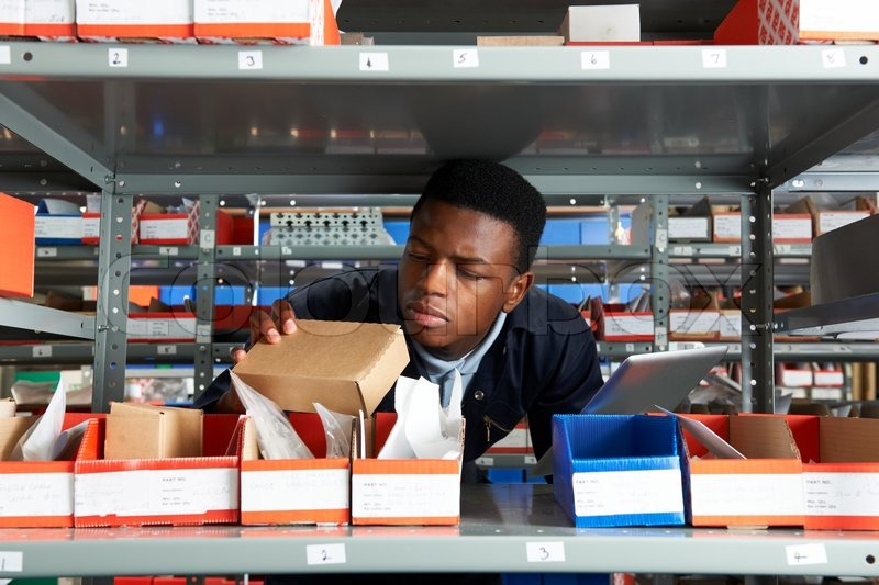 Factory Worker Using Digital Tablet In Store Room, stock photo