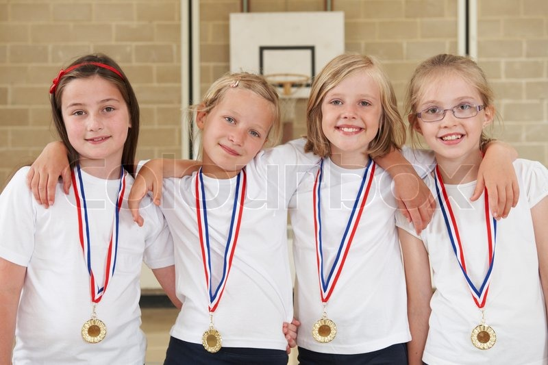 Female School Sports Team In Gym With Medals, stock photo