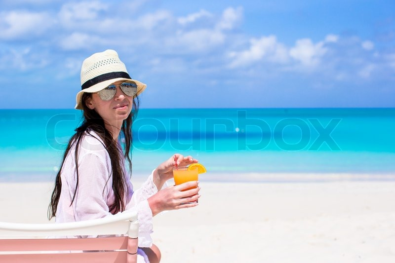 Stock image of 'Young woman enjoying the holiday spread her hands on a white, tropical beach'