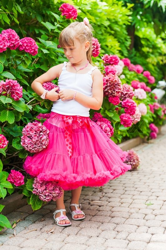 Beautiful little girl wearing bright pink tutu skirt and white top, standing next to bushes of hydrangea, vertical portrait, stock photo