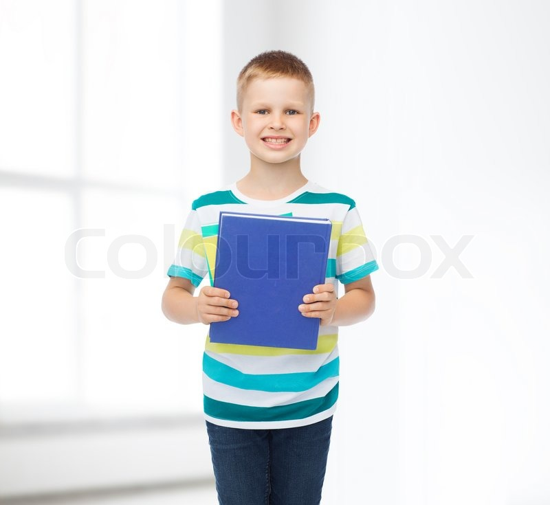 Education, childhood and school concept - smiling little student boy with blue book over white room background, stock photo