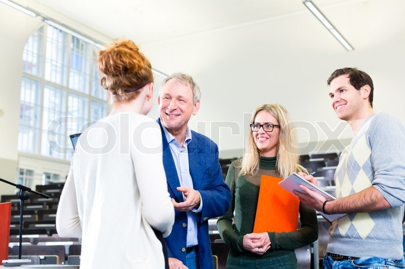 College students making lesson notes while asking professor in university auditorium, stock photo