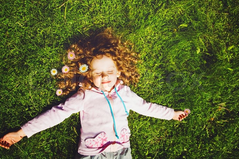 Curly girl lies on the grass and smiling, toning photo, stock photo