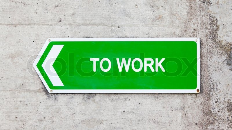 Green sign on a concrete wall - To work, stock photo
