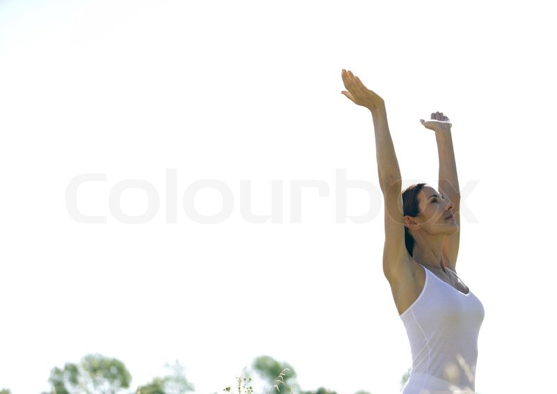 Side View Of A Woman With Arms Raised Stock Photo