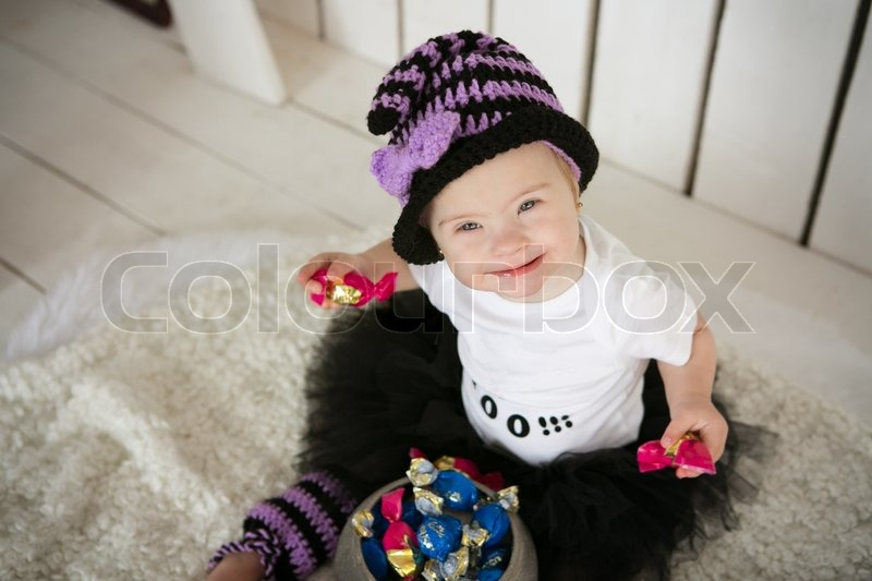 Girl with Down syndrome eating candy on a holiday halloween, stock photo