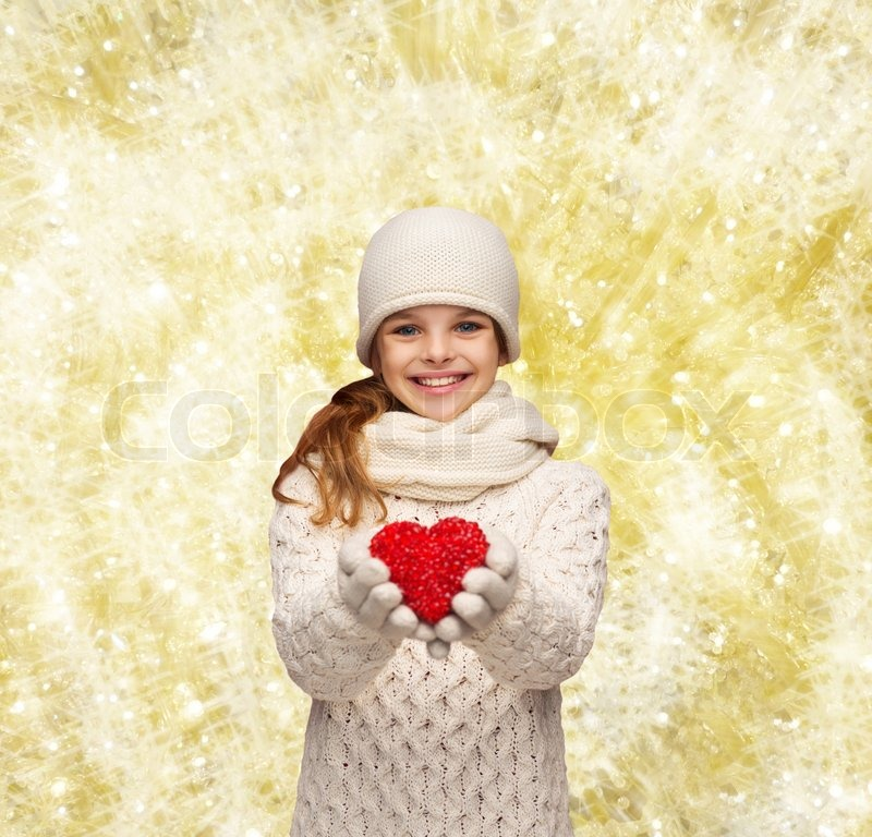 Christmas, holidays, childhood, presents and people concept - dreaming girl in winter clothes with red heart over yellow lights background, stock photo
