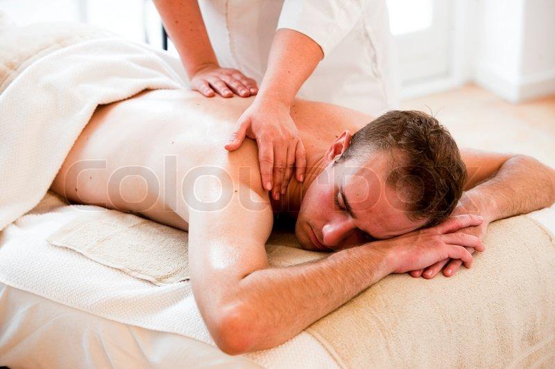 A male caucasian in a wellness spa getting massage, stock photo