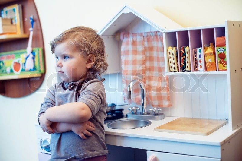 Stock image of 'toddler girl playing toy kitchen '