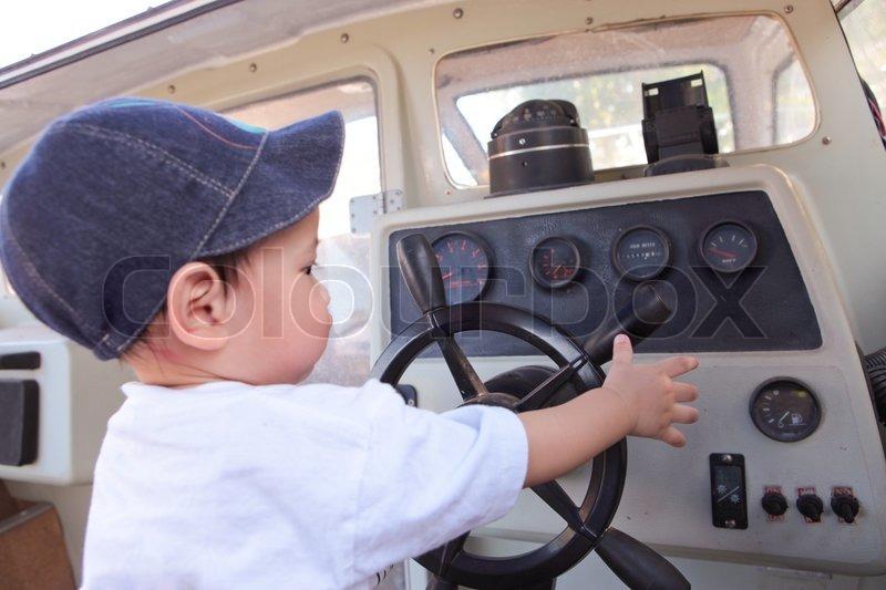 Little Boy Steering the Motor Boat, stock photo