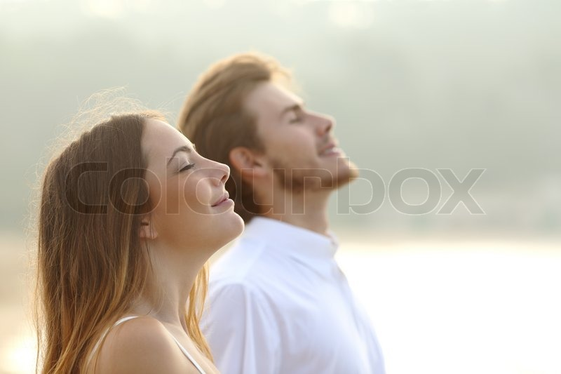 Profile of a couple of man and woman breathing deep fresh air together at sunset , stock photo